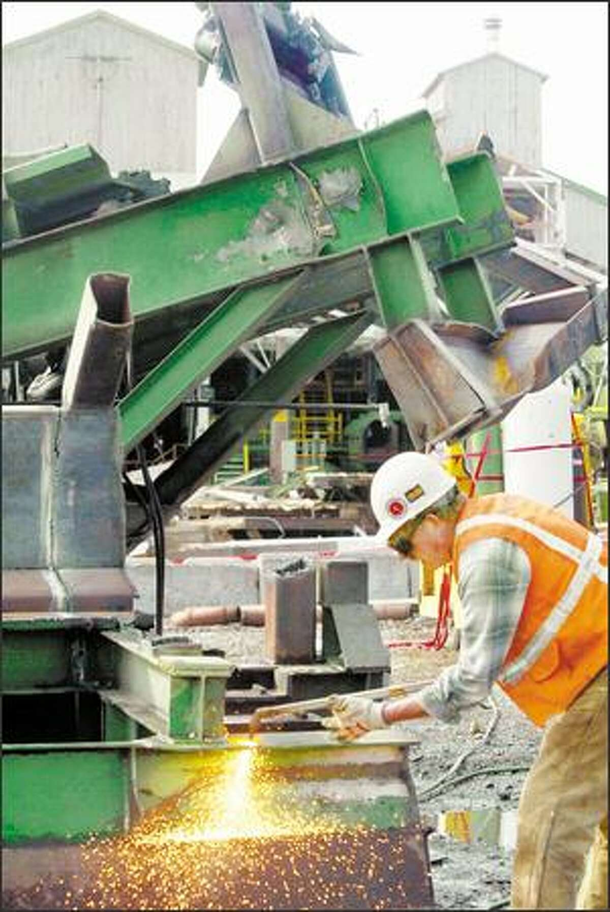John Schneider with Staton Cos., a demolition firm, cuts up a large steel beam that was removed from the closed Weyerhaeuser mill near Enumclaw. Steel, wood and even concrete will be salvaged and reused.