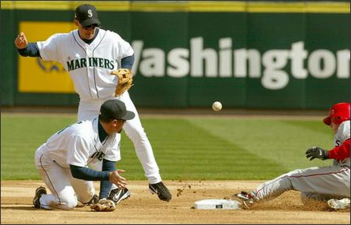 Rich Aurilia, the Mariners' new shortstop, makes an errant throw to Bret Boone after bobbling a grounder as Anaheim's David Eckstein slides safely into second base in the first inning.