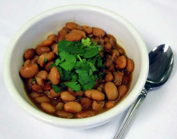 Frijoles a la charra instead of refried beans: Charro beans get the nod here, mostly because of their respective sodium content. A cup of charro beans has 643 grams sodium, while the refritos have 1,069 grams. You might think charro beans would be a lot more healthful than refritos, but most recipes add bacon, sausage and other goodies to add flavor, so the difference otherwise isn't that significant. A cup of charro beans has 197 calories and 1.34 grams total fat, while refrieds have 217 calories and 2.78 grams fat. Photo: WILLIAM LUTHER, Wluther@express-news.net / SAN ANTONIO EXPRESS-NEWS
