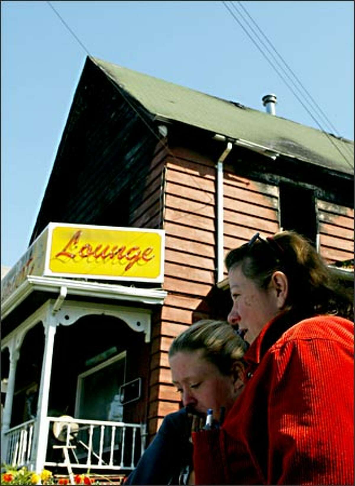 A relative comforts Sondra McCutchan, right, in front of the Cabbage Patch Restaurant in Snohomish Friday. Sondra has owned the restaurant for 26 years.