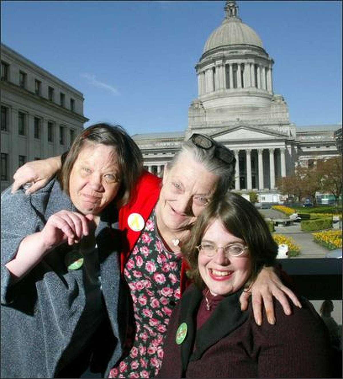 """Cherie Tessier, left, Diana Robishaw, center, and Emily Rogers are among the many people who worked on a bill in the Legislature's recent session promoting """"respectful language."""" Their lobbying effort included buttons."""