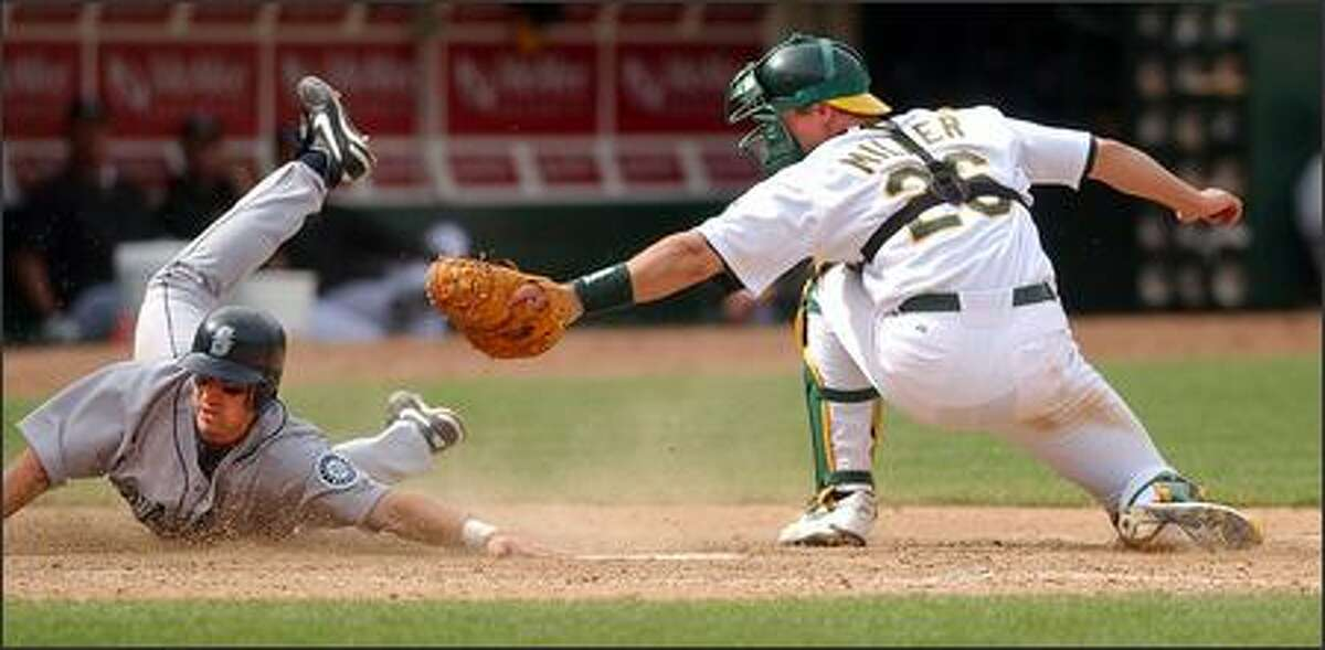 Willie Bloomquist slides safely beneath the tag off Oakland Athletics' catcher Damian Miller in the 10th inning in Oakland. The Mariners scored five times in the inning to defeat the A's 9-4 for their first win of the year. (AP Photo/Ben Margot)