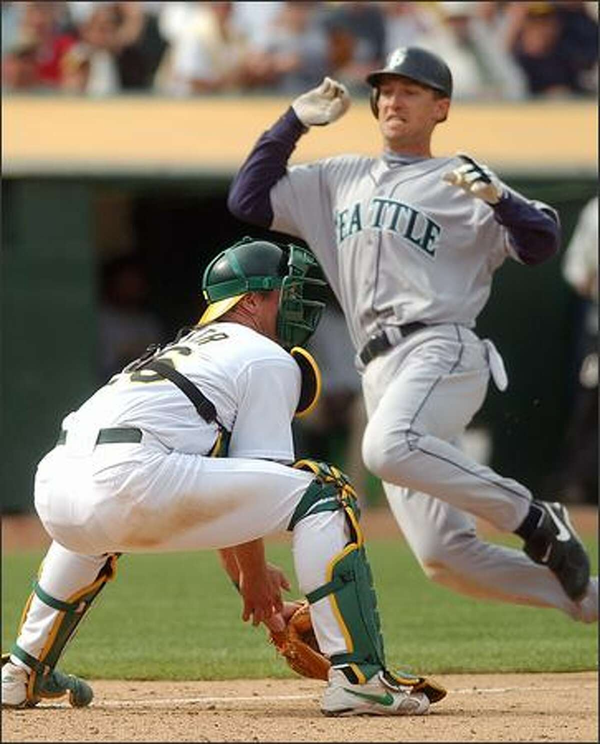 John Olerud goes into his slide as Oakland catcher Damian Miller waits for the throw during the 10th inning. Olerud scored on Willie Bloomquist's single.