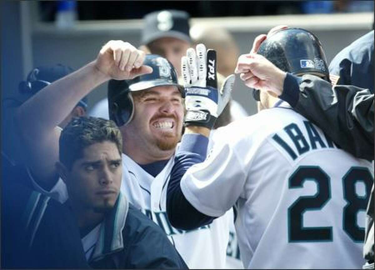 Raul Ibanez (28) was happy to see Scott Spiezio's smiling face after hitting a two-run homer off Rangers' reliever Erasmo Ramirez in the sixth inning to give the Mariners a 3-2 lead.