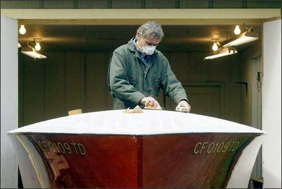 Hand sanding and 12 coats of painstakingly applied varnish go into each of the boats that Simon Fletcher builds at his Port Angeles workshop.