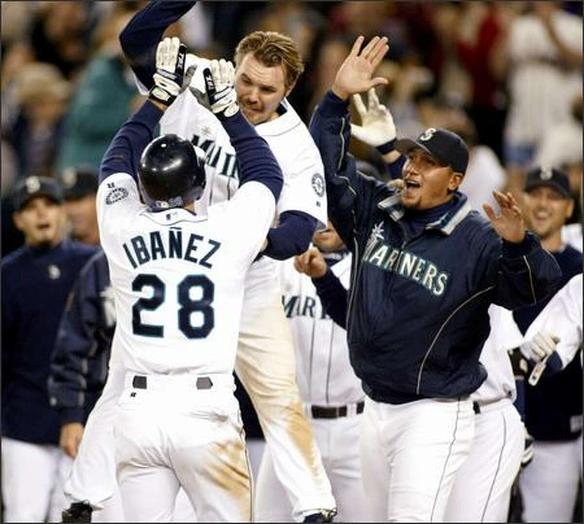 Raul Ibanez is greeted by Scott Spiezio, top, and Freddy Garcia, right, after hitting a walk-off home run in the ninth inning. Ibanez hit a 2-2 pitch off Jim Mecir to right field.