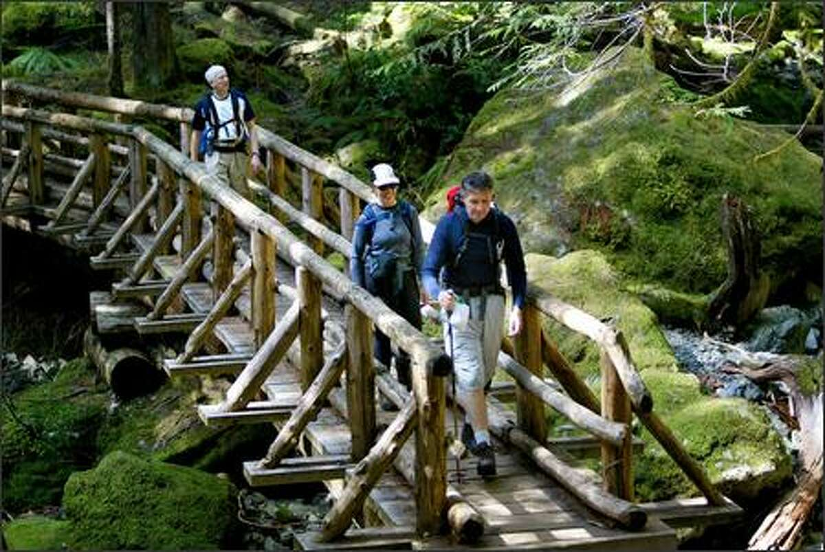A babbling brook and moss-cushioned boulders enhance a fairy-tale scene as Mountaineers club trip leader Doug Terry of Silverdale and fellow club members stride across a rustic footbridge along the Lena Lake Trail.