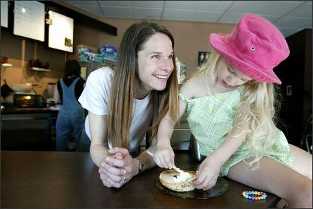 Julie Parker, owner of My Coffeehouse in Madison Park, has H&H Bagels shipped from New York, much to the delight of 3-year-old Piper Shethar.