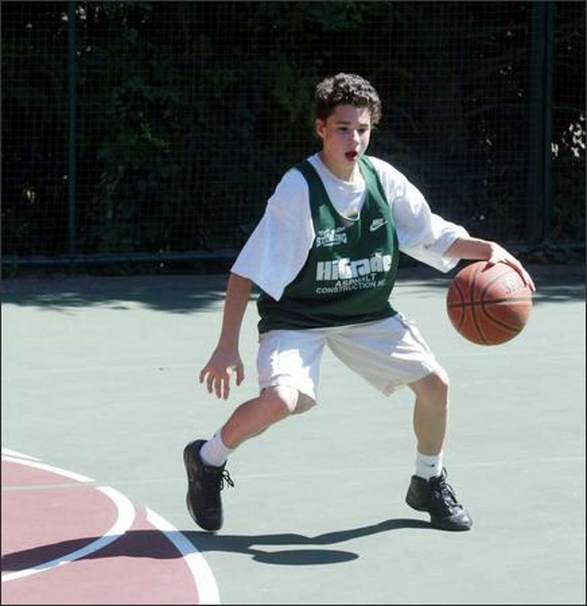 Anthony plays basketball on the court in his backyard.