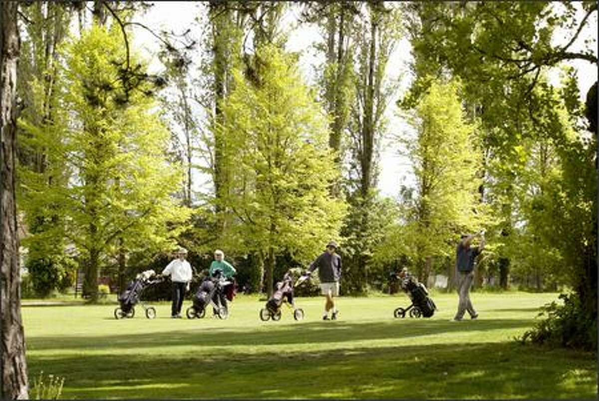 Golfers and trees line the 11th fairway as the golfers watch the flight of the ball at Jefferson Golf Club in Seattle.