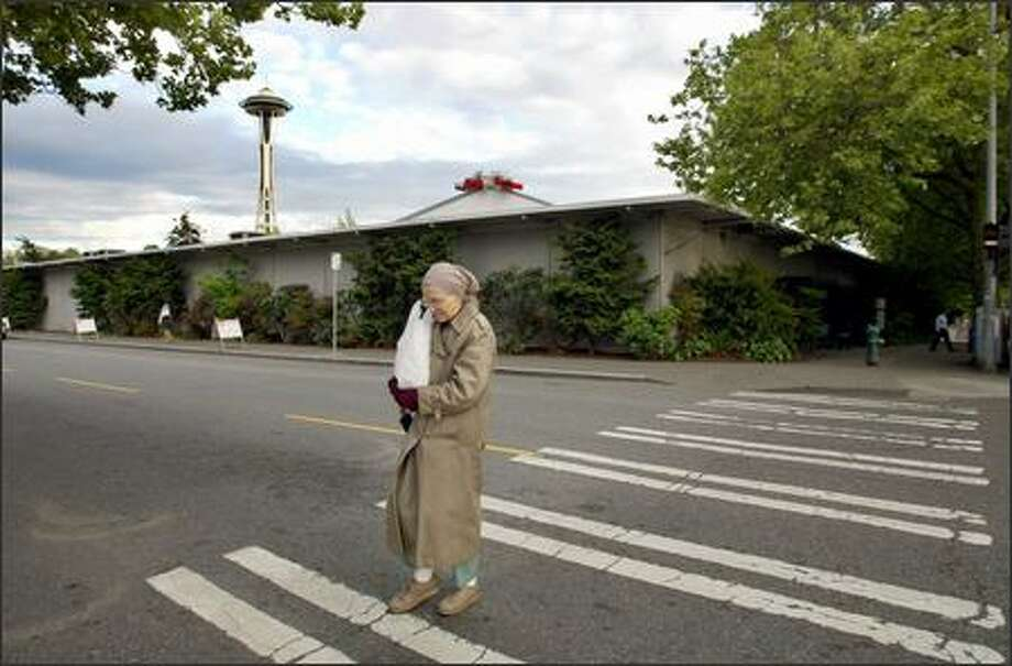 A pedestrian walks across Republican Street on First Avenue North past the Seattle Center's north conference buildings, some of which will be displaced by a monorail route approved yesterday. Photo: Gilbert W. Arias/Seattle Post-Intelligencer