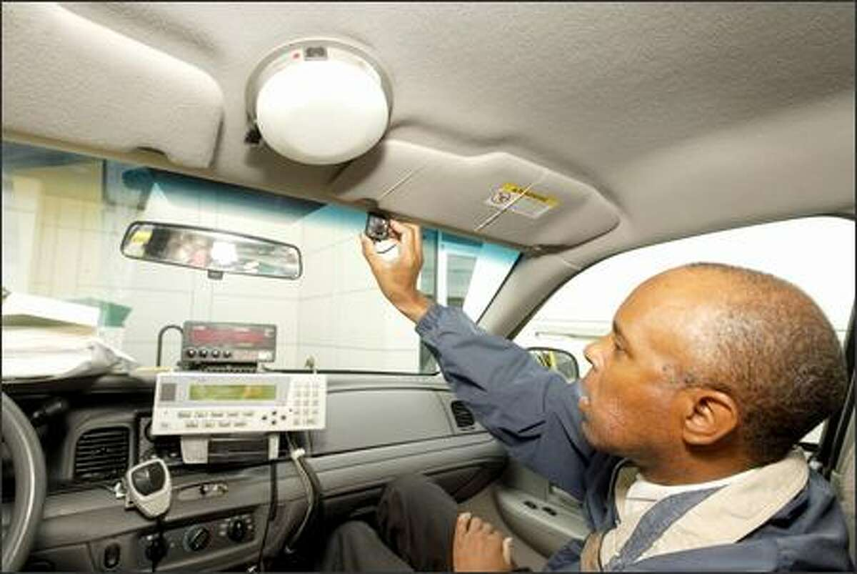 Terry Davis, who has driven a cab for 15 years, shows the media yesterday a small camera that has been installed in a Yellow Cab.