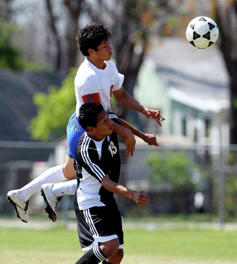 Jefferson's Noe Rodriguez (09) directs a header over Edison's Darren Gonzalez (13) in boys soccer at San Antonio ISD Spring Sports Complex on Tuesday, Mar. 15, 2011. Rodriguez scored two of the three goals as Jefferson defeated Edison, 3-1. Photo: Kin Man Hui/kmhui@express-news.net / San Antonio Express-News