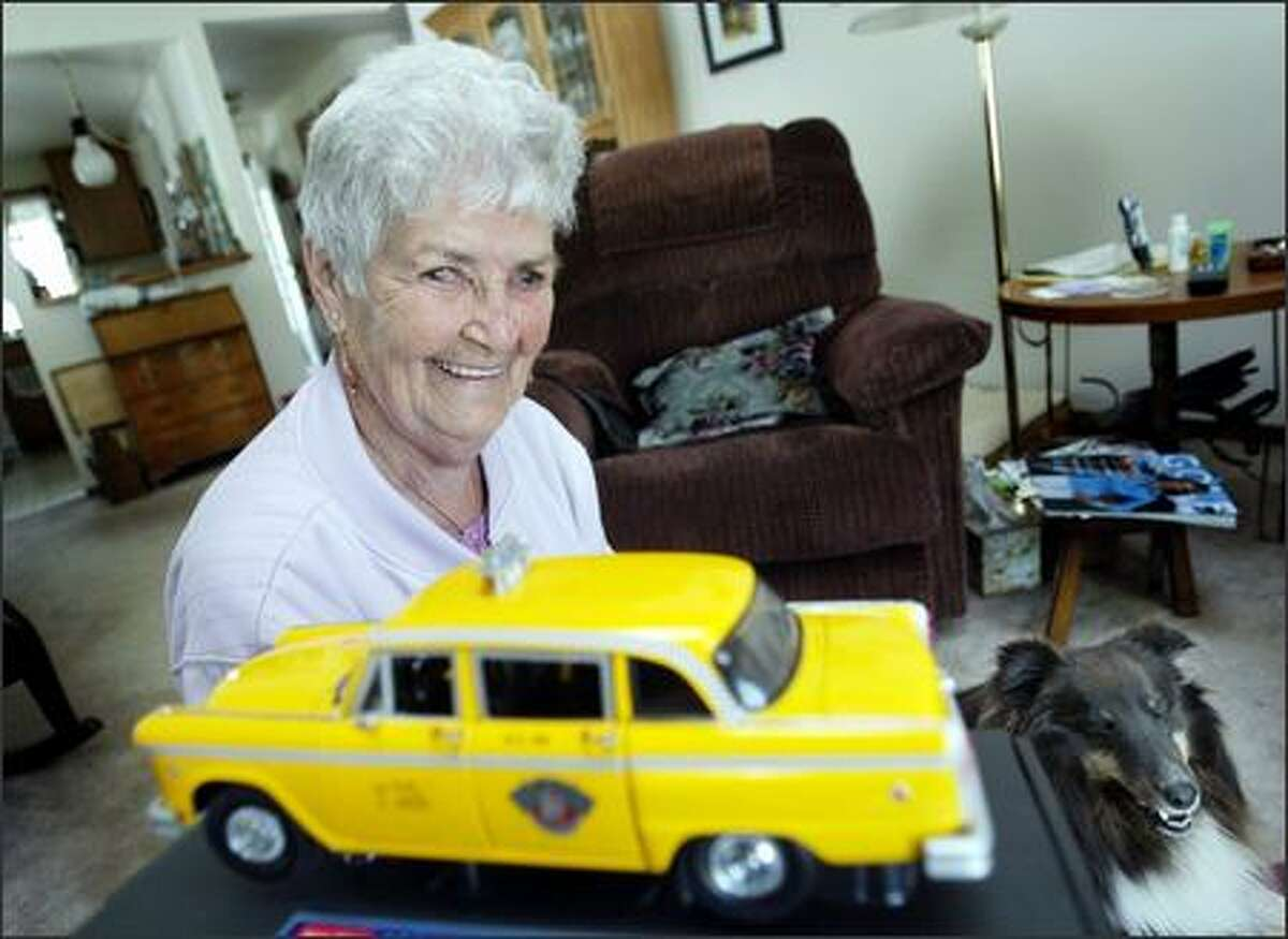 At home in Parkland with her dog Skiddles, Nadine McKee Henry, 85, poses with a reminder of her wartime cab-driving adventure in Seattle. When the war ended, so did her job.