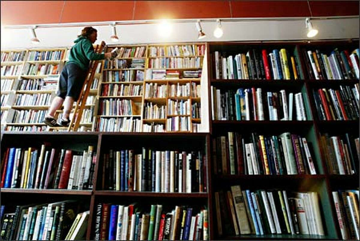 Customer Tina Bechler of Seattle browses the top shelves of used books at Bookworm Exchange, a used bookstore that opened recently in Columbia City.