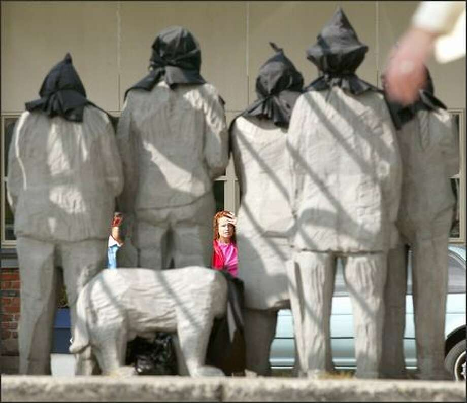 "The figures in Fremont's ""Waiting for the Interurban"" sculpture were hooded yesterday, a reference to the recent prison-abuse photos from the war in Iraq. Photo: Mike Urban/Seattle Post-Intelligencer"