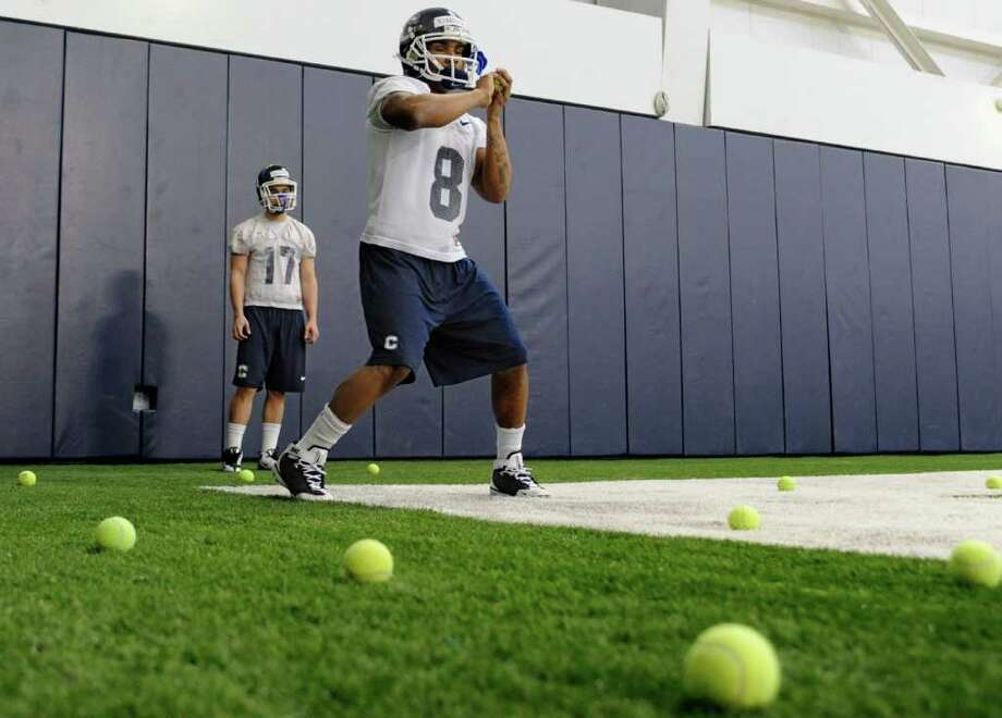 Connecticut wide receiver Leon Kinnard (8) catches tennis balls thrown toward him from a machine while teammate Frank Guardi (17) looks on during the first day of spring NCAA college football practice in Storrs, Conn., Tuesday, March 15, 2011  (AP Photo/Jessica Hill) Photo: AP