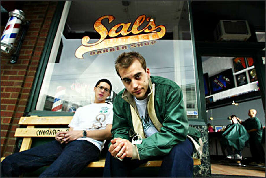 Sal's Barber Shop owners Brian Rauschenbach, left, and Marcus Lalario have groomed their business to cater to the hip-hop crowd, with music in the air and memorabilia on the walls. Photo: Karen Ducey/Seattle Post-Intelligencer