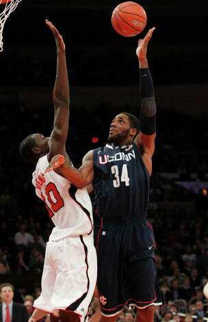 Connecticut's Alex Oriakhi (34) shoots over Louisville's Gorgui Dieng (10) during the first half of an NCAA college basketball game at the Big East Championship ,Saturday, March 12, 2011, in New York. (AP Photo/Frank Franklin II) Photo: AP