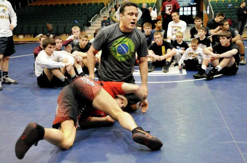 Brazilian jujitsu master Renzo Gracie, center, shows a move on former wrestler Frankie Edgar as the Ultimate Fighting Championship holds a demonstration on Tuesday, March 15, 2011, at the Washington Avenue Armory in Albany, N.Y. (Cindy Schultz / Times Union)
