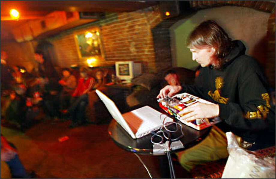 Kris Moon wows the crowd at Pioneer Square's Temple Billiards with his mixing prowess on the Macintosh iBook. Moon and fellow artists Steven Ford and Zach Huntting came up with the idea of staging laptop battles along the West Coast. Photo: Joshua Trujillo/Seattle Post-Intelligencer