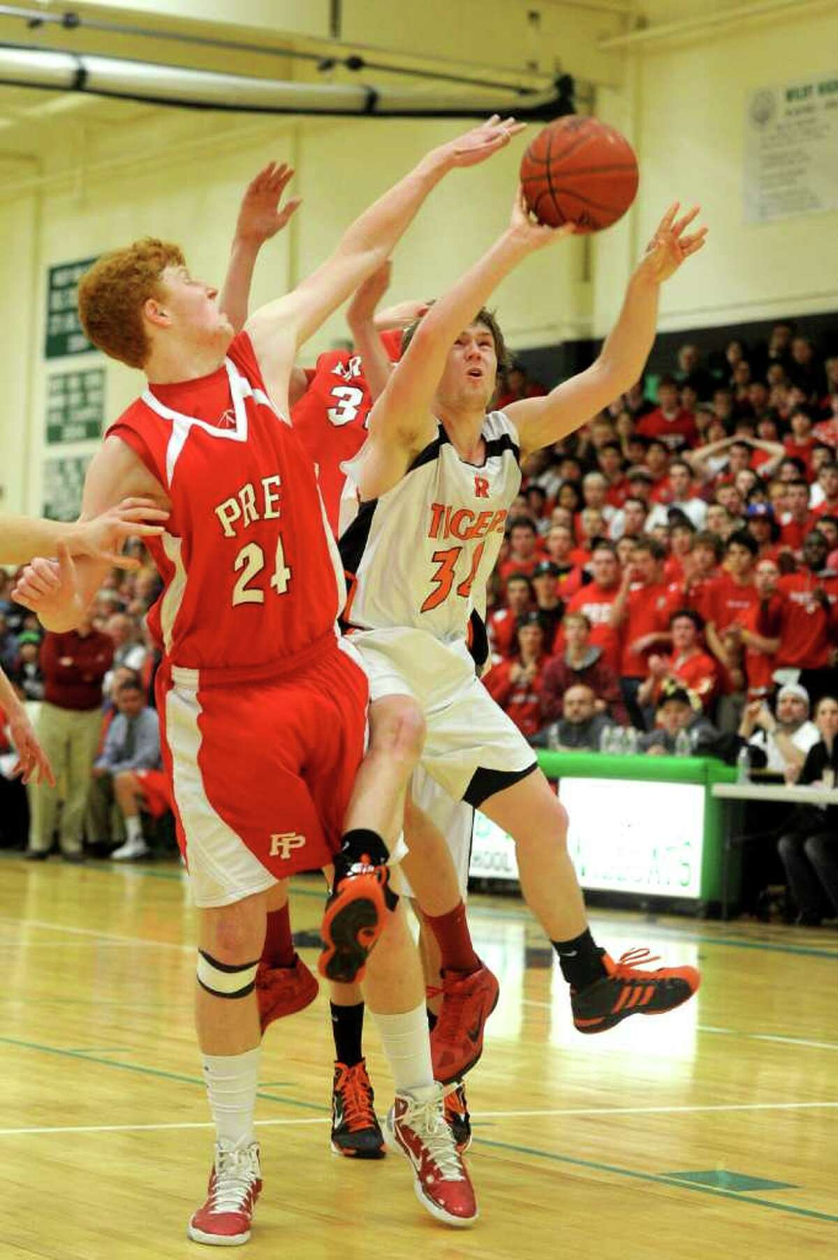 Ridgefield's Bryan Galvin takes a shot as Fairfield Prep's Alex Heiman defends during Tuesday's class LL semifinal game at Wilby High School in Waterbury on March 15, 2011.
