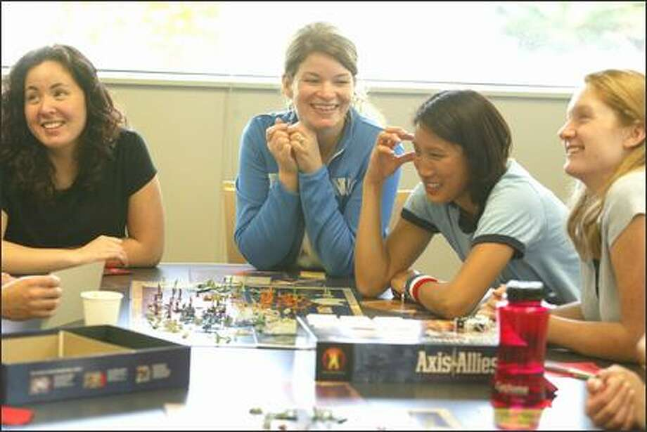 Wizards of the Coast employees, from left, Lisa Hanson, Kate Irwin, Mia Brooks and Jennifer Lathrop, play Axis & Allies, one of the company's many games, at their Renton office. The company, whose games attract primarily male players, is expanding its market with a card game, Star Sisterz, targeting girls. Photo: SCOTT EKLUND/P-I
