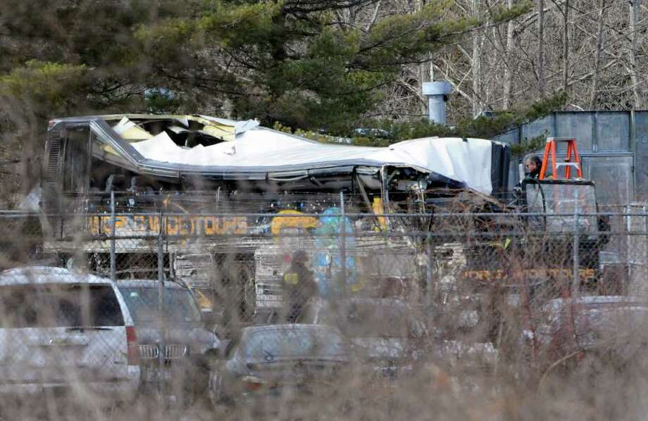 NTSB workers inspect the tour bus at a New York State Police impound lot in Salt Point, N.Y. Tuesday, March 15, 2011  (AP Photo/Bill Kostroun) Photo: Bill Kostroun