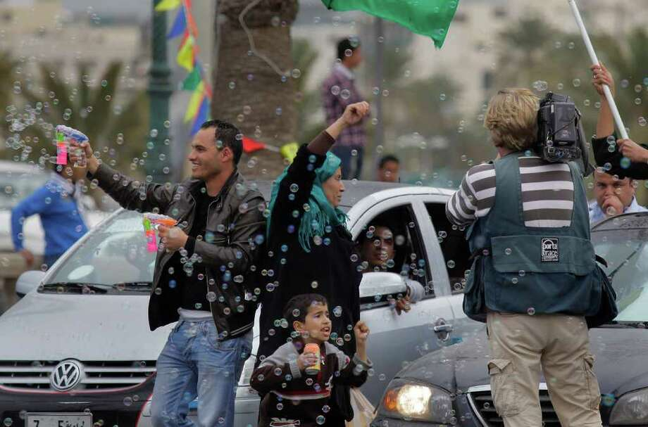 Following the announcement on Libyan state television  that Moammar Gadhafi's forces took the Eastern city of Ajdabiya, Gadhafi supporters celebrate on Green Square in Tripoli, Libya, Tuesday March 15, 2011.  Government forces struck the rebellion's heartland with airstrikes, missiles and artillery on Tuesday, trying for the first time to take back a city that serves as a crucial gateway for the band of fighters who threatened his four-decade hold on power. (AP Photo/Jerome Delay) . (AP Photo/Jerome Delay) Photo: Jerome Delay / AP