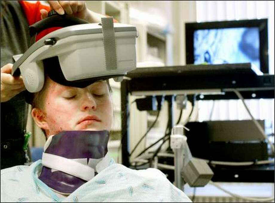 Burn victim Shandra Clark, 13, of Kalispell, Mont., makes use of virtual-reality technology during a therapy session at Seattle's Harborview Medical Center. Photo: Dan DeLong/Seattle Post-Intelligencer
