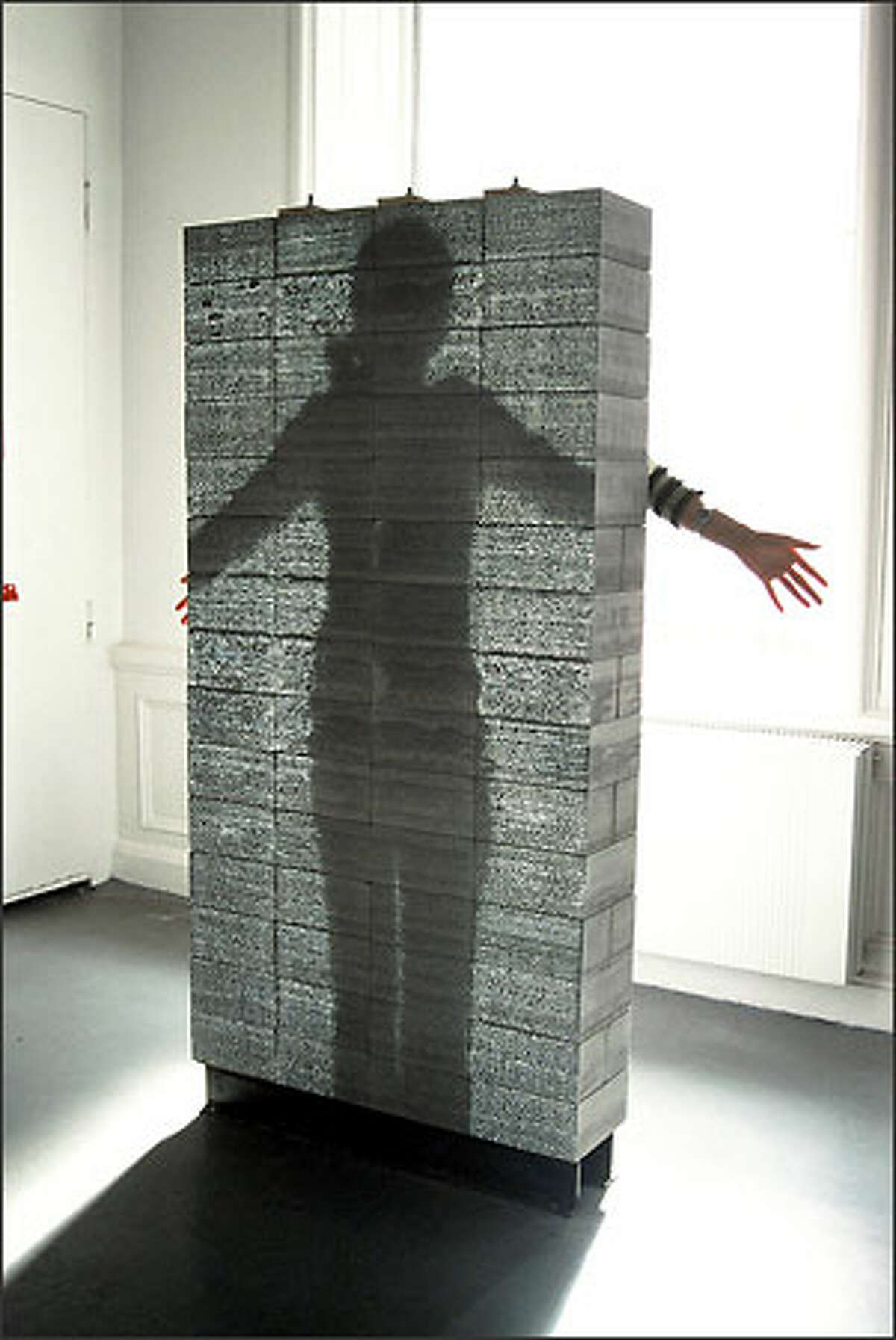 A prototype wall of translucent concrete is shown at the National Building Museum. When backlit, a human form can be seen through the wall. The blocks are made by mixing glass fibers into the combination of crushed stone, cement and water.