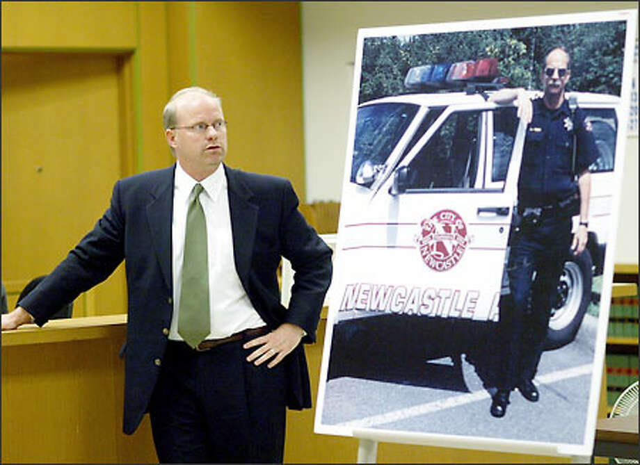 Prosecutor Tim Bradshaw shows the jury a photo of slain Deputy Richard Herzog. Prosecutors say Matthews killed Herzog because he was high on crack, not because he is insane, as the defense contends. Photo: Dan DeLong/Seattle Post-Intelligencer