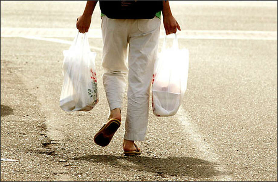 A shopper carries two of an estimated high of 1 trillion bags used annually. Photo: Mike Urban/Seattle Post-Intelligencer