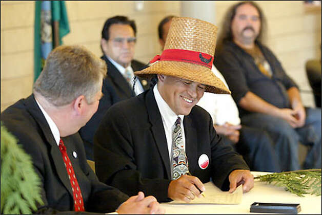 "Seattle Mayor Greg Nickels, watches as the Swinomish Chairman Brian Cladoosby signs ""government-to- government"" agreements. Also signing with the city were the Tulalips, the Suquamish and the Snoqualmie Photo: Scott Eklund/Seattle Post-Intelligencer"