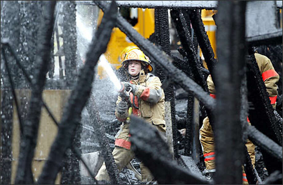Seattle firefighter Patricia Mann douses a hot spot yesterday at the fire that engulfed an apartment building under construction in the Wallingford neighborhood. Photo: Scott Eklund/Seattle Post-Intelligencer
