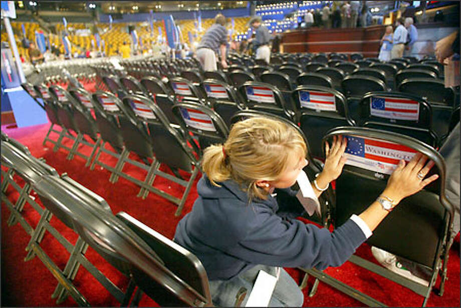Lilly Higgins of Boston puts signs up identifying the Washington delegates' section at FleetCenter in preparation for the Democratic convention. Photo: Karen Ducey/Seattle Post-Intelligencer