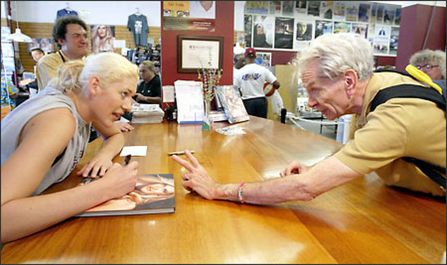 "Lauren Jackson signs a copy of Athens Dream for Ed Mignon, who asked the Storm star to personalize it by writing ""To Ed"" on the cover. Photo: Scott Eklund/Seattle Post-Intelligencer"