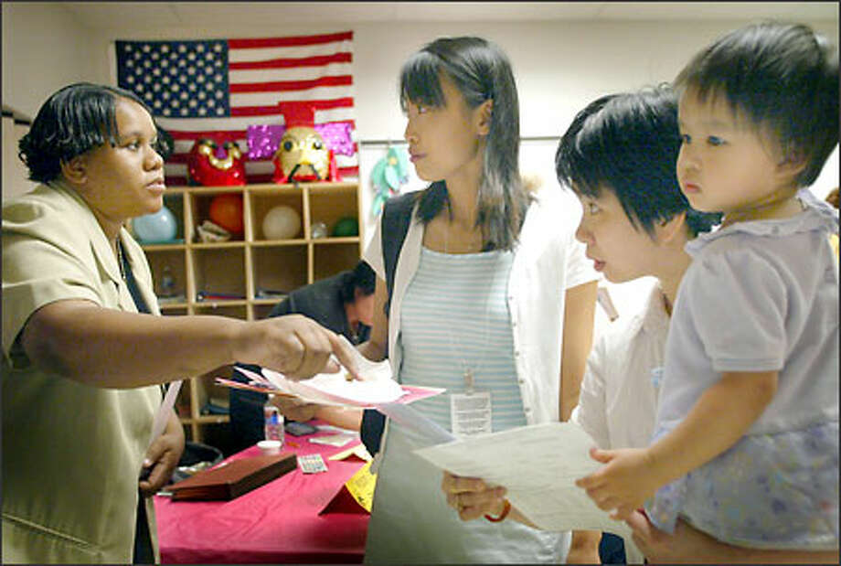 Lin Lei Ross, a Red Cross Language Bank translator, center, helps Wanna Huang and her 2-year-old daughter Laura talk with Christine Wiley, left. Photo: Joshua Trujillo/Seattle Post-Intelligencer
