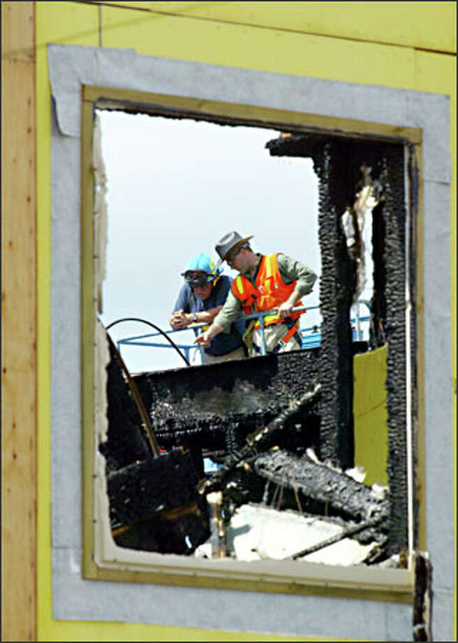 A Seattle Fire Department investigator, left, and crane operator Jim Amphlett view the remains of the condo construction site at North 61st Street and Phinney Avenue North. Damage was estimated at $3 million. Photo: Grant M. Haller/Seattle Post-Intelligencer