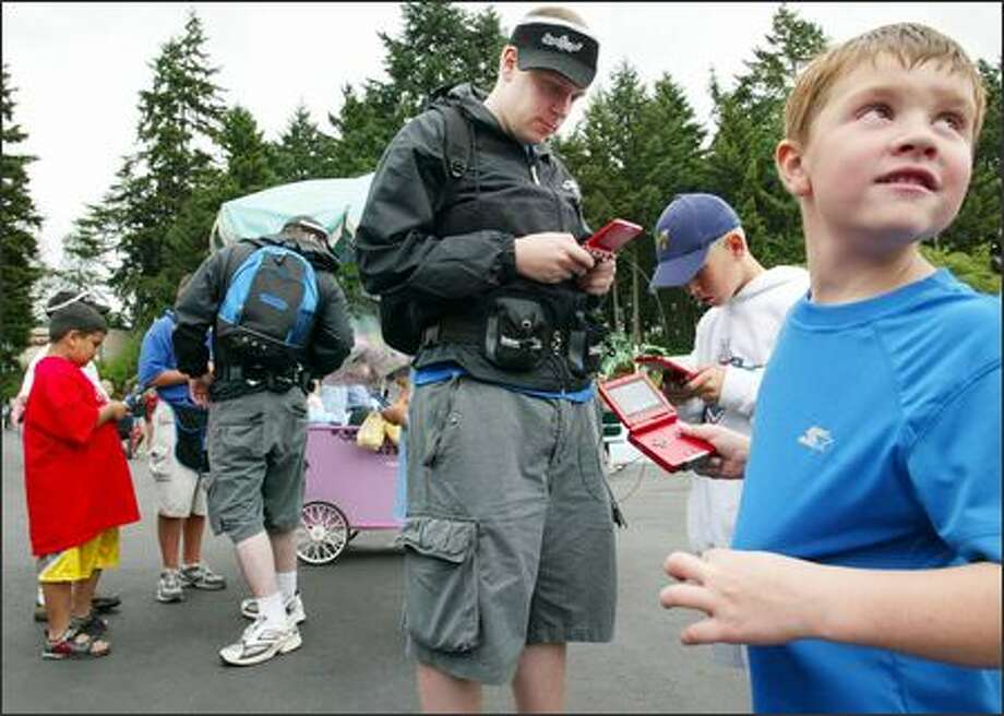 Joseph Maney, 6, tries out a game with help from Christian Snook, center, at a recent visit to Wild Waves. Snook is part of the Nintendo Street Team in Seattle. Photo: PAUL JOSEPH BROWN/P-I