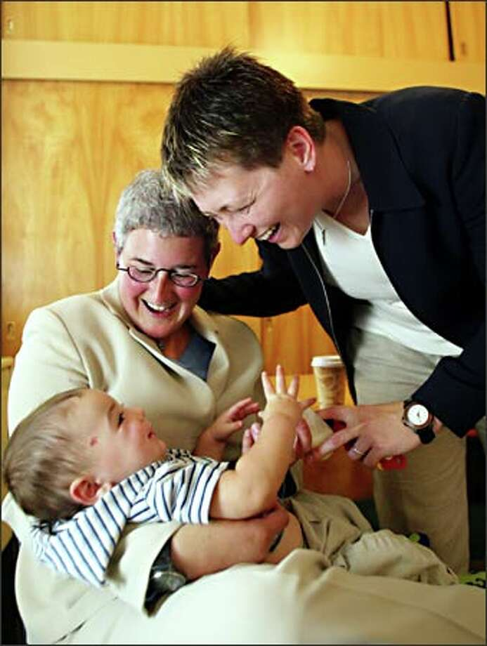 "Johanna Bender, left, and Sherri Kokx enjoy a moment with son Quin, 7 months, after a news conference yesterday about Superior Court Judge William Downing's ruling that same-sex couples have a ""fundamental right"" to marry. Photo: Dan DeLong/Seattle Post-Intelligencer"
