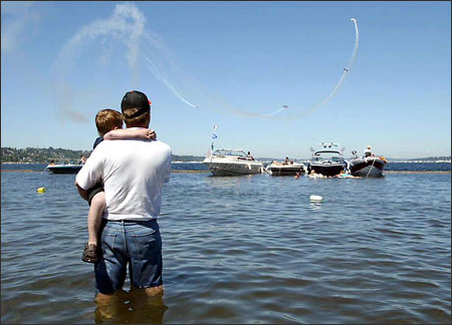 A man and his 6-year-old son watch the Red Baron Pizza Squadron perform at the Chevrolet Cup at Seafair on Lake Washington. Photo: Joshua Trujillo/Seattle Post-Intelligencer