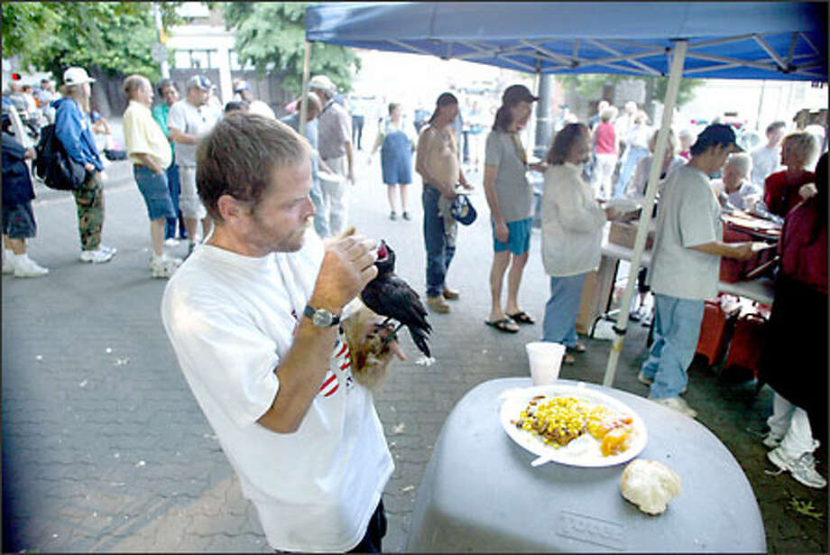 Rick Hunter, who says he is penniless, shares his dinner with his pet crow, Lucky, and his dog, Baby, after they went through the food line at City Hall Park last night. Photo: Karen Ducey/Seattle Post-Intelligencer