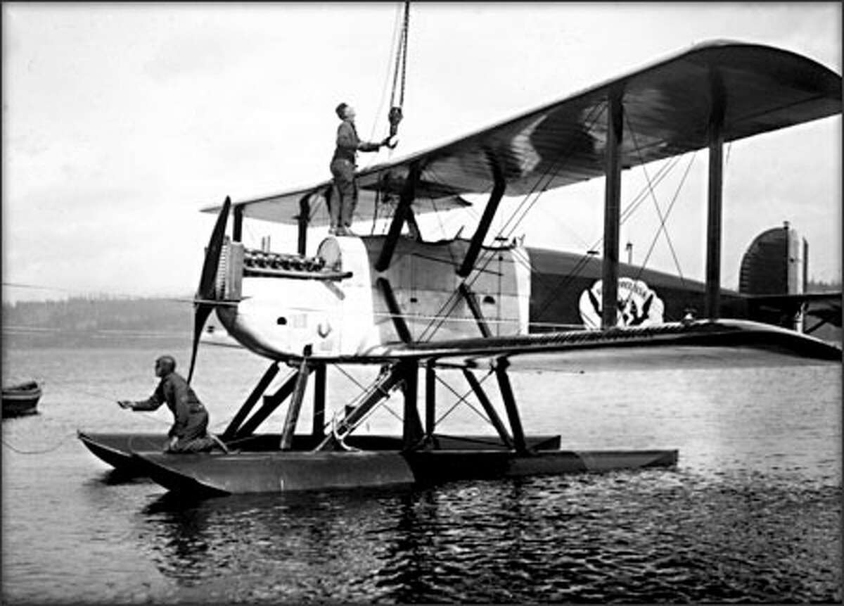 With Maj. Frederick Martin on the pontoon and Sgt. Alva Harvey on the fuselage, the World Flight team's flagship biplane, Seattle, readies for takeoff from Lake Washington on April 6, 1924. (PHOTOS COURTESY OF MOHAI AND PEMCO WEBSTER & STEVENS COLLECTION)