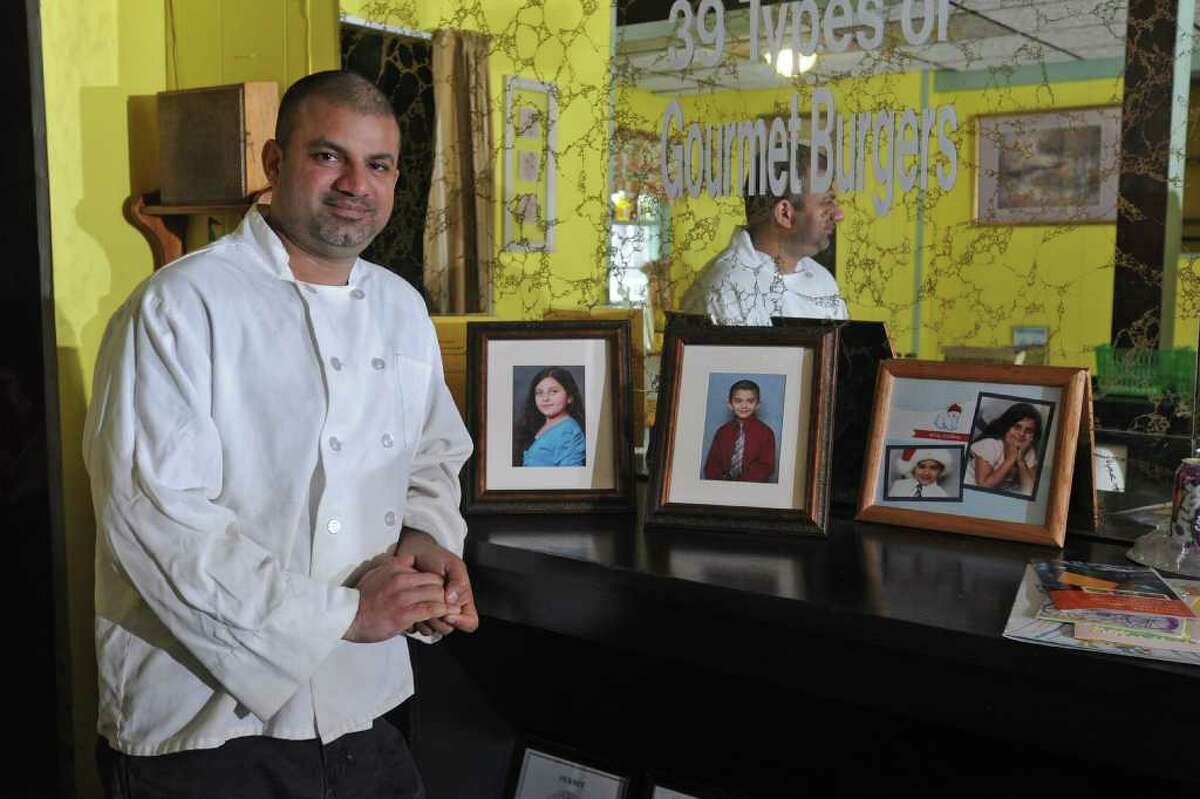 Faisal David Khan stands next to photos of his children at his restaurant Burger Centric in Albany, NY on Thursday, March 10, 2011. (Lori Van Buren / Times Union)