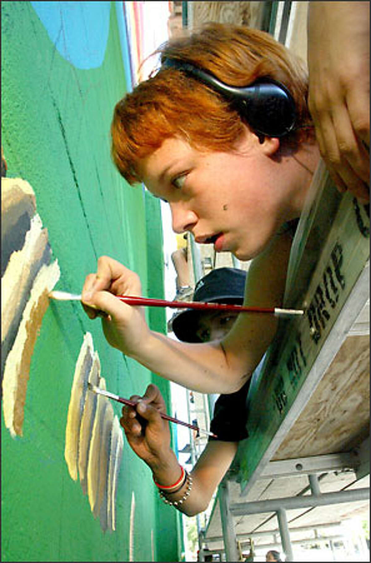 """Meredith Billington, 17, helps paint a mural on the side of the New Horizons Ministries drop-in center in Belltown. Titled """"Pulling Back the Veil,"""" the mural explains """"to the world what street life means to us,"""" Billington said."""
