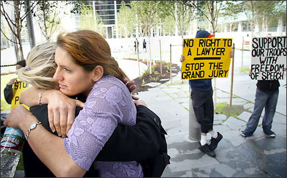 Animal rights activist Gina Lynn, facing camera, gets a hug from friend and fellow activist Allison Lance Watson while standing with supporters outside the U.S. Courthouse in Seattle yesterday. Lynn later refused to testify before a federal grand jury investigating a firebombing at an Olympia timber company. Photo: Dan DeLong/Seattle Post-Intelligencer