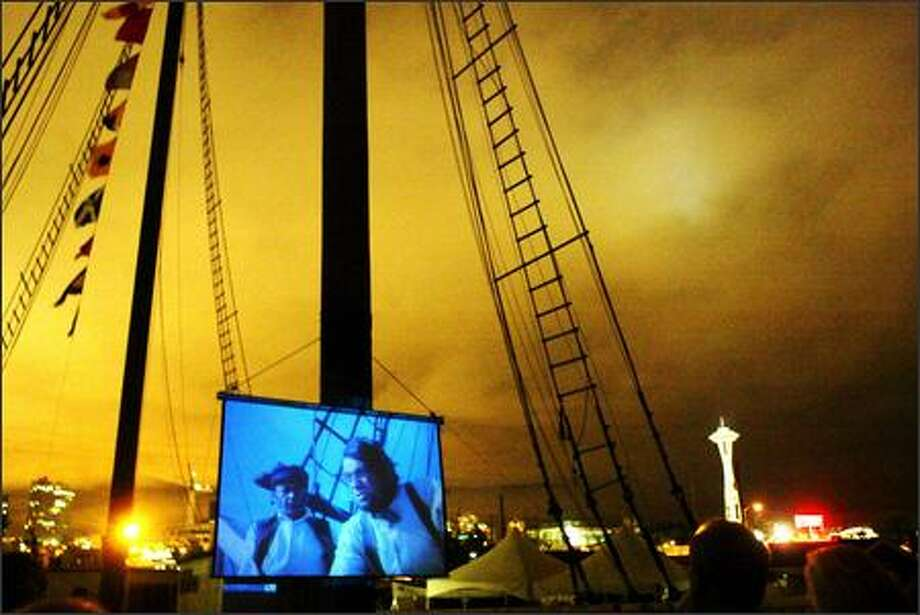"""Visitors aboard the Wawona enjoy a screening of """"Moby Dick"""" and a twinkling Seattle skyline as seen from south Lake Union. Northwest Seaport, the organization that owns the vessel, shows classic maritime films on its main deck on selected weekends. The movies are free, but donations are gladly accepted and desperately needed. Photo: Karen Ducey/Seattle Post-Intelligencer"""
