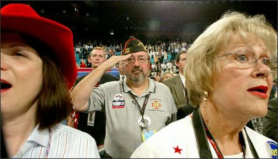 David Lemak of Kennewick recites the Pledge of Allegiance yesterday with other Washington delegates, including Karen Steele of Normandy Park, left, and Joan Dehn of Burien. Photo: Karen Ducey/Seattle Post-Intelligencer