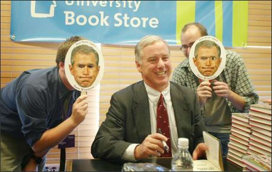 Howard Dean signs books at University Book Store yesterday as Matthew Simmons, left, and Stuart Bloomfield jump behind him and hold up promotional masks for a new book about President Bush while a friend snaps a picture. Photo: JOSHUA TRUJILLO/P-I